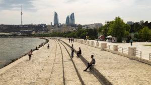Odpočinek u Kaspického moře na bulváru v Baku. V pozadí mrakodrapy Flame Tower.