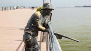 Socha rybáře na molu. Ten by tu ale pravděpodobně žádnou rybu nechytil. Ovšem v případě, že tu nežije Ropák bahnomilný!
