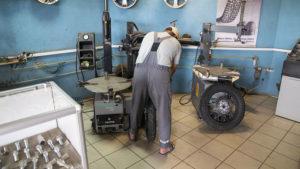 Mechanik v pneuservisu se marně snaží přezout přední plášť.